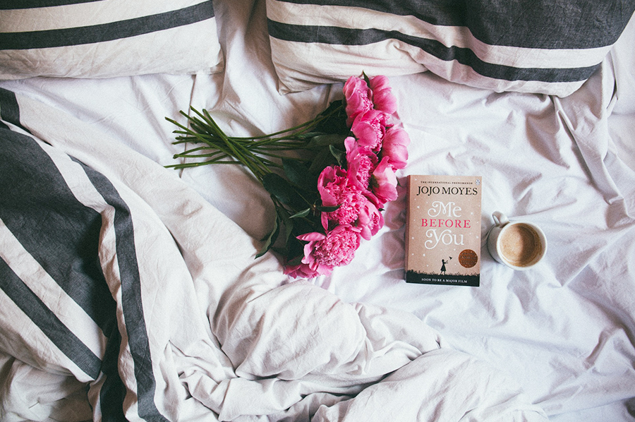An image of some flowers, a book, and coffee on a bed